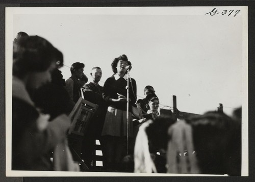 Yo Ikeda raises her beautiful voice during ceremonies which open the football game between Topaz and Fillmore high schools at Topaz Relocation Center, November 11, 1943. Topaz, Utah