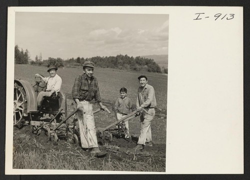 B. Fujii and his sons Ed, Tom, and Ted (voluntary evacuees to Weiser, Idaho) are shown cultivating their asparagus field