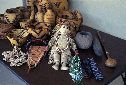 Baskets, doll, necklace, rattle, and stone tools