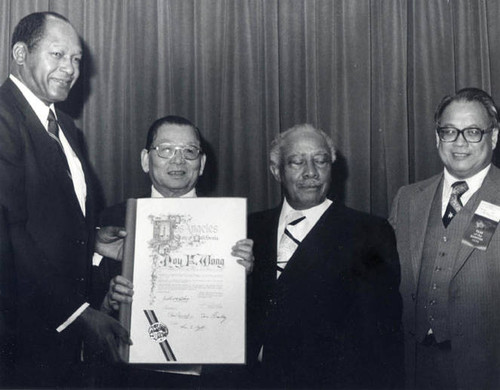 Poy Wong receiving a certificate from Mayor Tom Bradley and Councilmember Gilbert Lindsay with Irvin Lai on the right