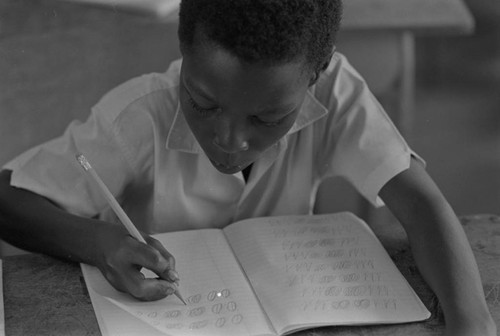 Student in a classroom writing on notebook, San Basilio de Palenque, ca. 1978