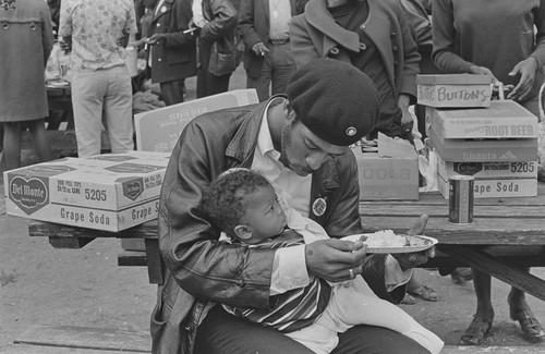 Black Panther feeding son, at Free Huey Rally, De Fremery Park, Oakland, CA, #29 from A Photographic Essay on The Black Panthers
