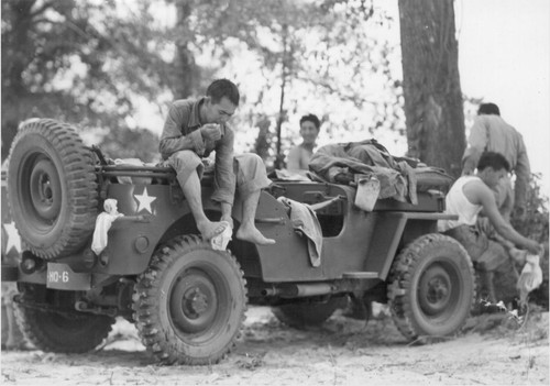 Hot Mississippi. Members of the 442nd combat team drape themselves on a jeep to dress after a cool swim in