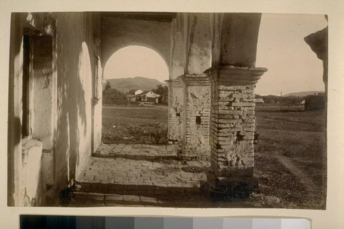 [Mission, possibly San Juan Capistrano, looking out toward hill]
