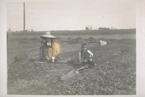 [Japanese mother and son working in a field.]