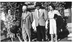 Charles R. and Eva Myers and an unidentified couple standing outside a vine-covered house or building in 1945