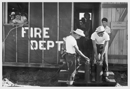 Army type fire extinguishers are being examined by evacuees Eiichi Omori and George Nakamura at this War Relocation Authority center.--Photographer: Clark, Fred--Poston, Arizona. 5/25/42