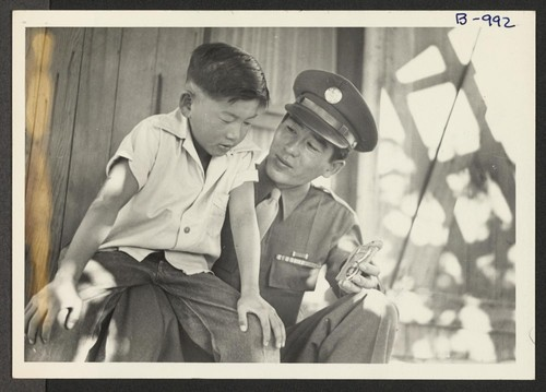 Sgt . Kazuo Komoto, veteran of Guadalcanal and New Georgia, shows his medal, the Purple Heart, to his younger brother, Susumu, while visiting his parents at the Gila River Relocation Center near Phoenix, Arizona. Rivers, Arizona