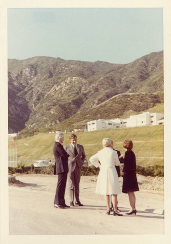 Bob Bales, President Banowsky, Peggy Bales, John McCarty, Mrs. Young with the Student Housing and mountains in the background