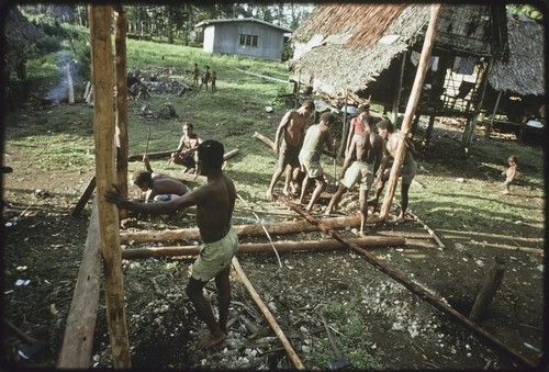 House-building: men build frame for a new house, putting in vertical supports