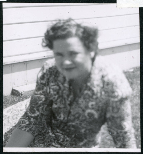 Photograph of Lucy Adams sitting on the grass in front of staff housing at Manzanar