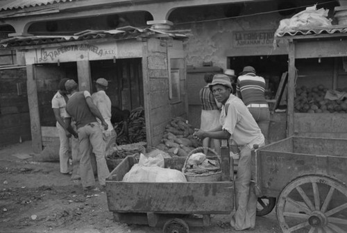 Man resting his arms on a cart at city market, Cartagena Province, ca. 1978