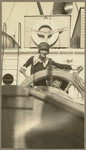 [Woman posing at ship's wheel on the Admiral Dewey]