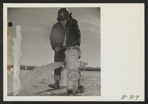 Mike Yoshimine, an evacuee member of the Fire Department, makes a routine check of a fire hydrant to see that pressure is sufficient to handle any emergency. This flow test is made once a week. Photographer: Stewart, Francis Topaz, Utah