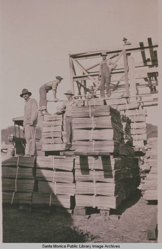 Carpenters and workmen pile lumber at Construction Center, Assembly Camp in Temescal Canyon, Pacific Palisades, Calif