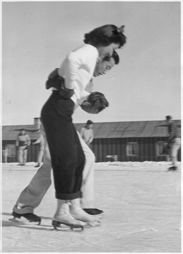 A young hopeful, not yet quite sure of himself on ice, attempts to show his best girl some of the intricacies of ice skating. For former Californians of Japanese ancestry, now residing at Heart Mountain, ice skating was a new thrill. Photographer: Parker, Tom Heart Mountain, Wyoming