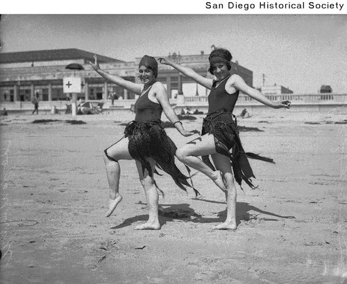 Bobbie Harmon and Mary Malloy posing on a beach wearing bathing suits adorned with kelp
