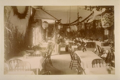 [Room decorated for a banquet, with plants, garlands, tables, and chairs]