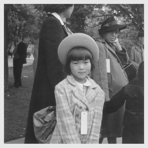 Hayward, Calif.--A young member of an evacuee family awaiting evacuation bus. Evacuees of Japanese ancestry will be housed in War Relocation Authority centers for the duration. Photographer: Lange, Dorothea Hayward, California