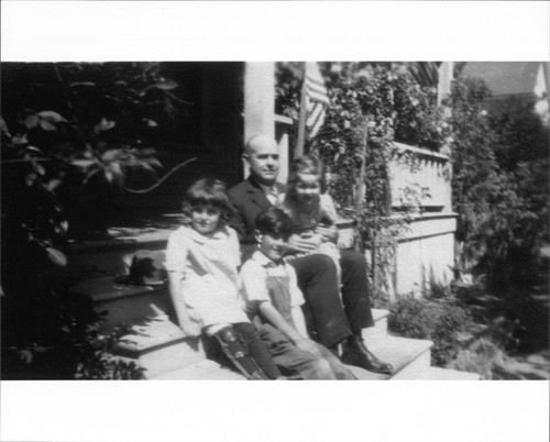 Walter Neil sitting on the front porch at 231 Wilson Street, Petaluma, California with his daughter, niece and nephew, about 1929