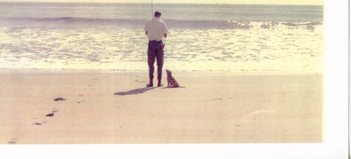Dale Smith fishing on the beach with a puppy