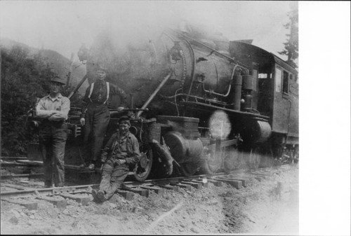 Three men at the front of a lumber train locomotive, June 13, 1914