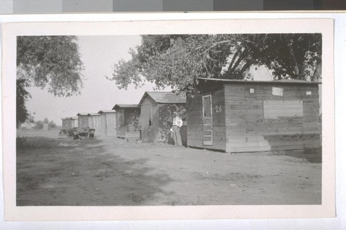 July, 1936, Kern County, Kern Lake District. The typical laborer cabins. The Deputy Health Officer of Kern County is standing near the cabin