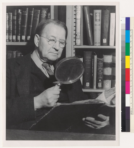 [Herbert E. Bolton examining a volume with a magnify glass.]