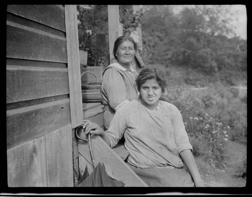 Two unidentified Native American women sitting on steps of a house