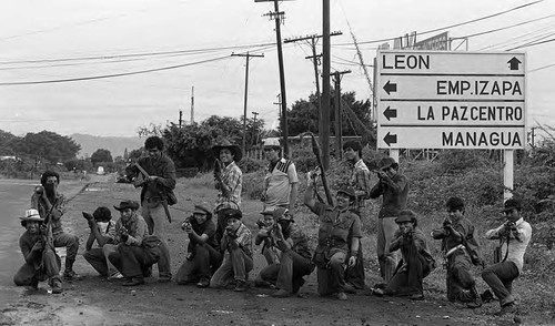 Sandinistas pose in front of a road sign, Nicaragua, 1979