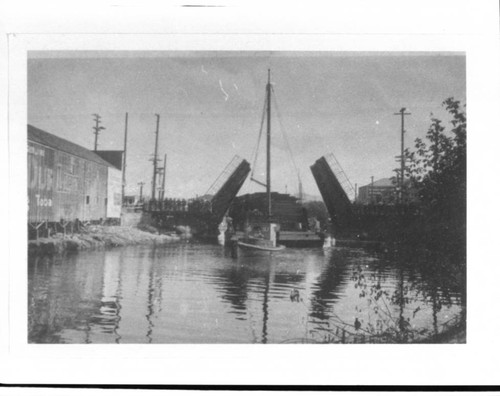 Tug towing a barge under the D Street drawbridge, Petaluma, California, about 1925