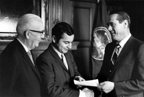 Two men receiving a check from Reinecke