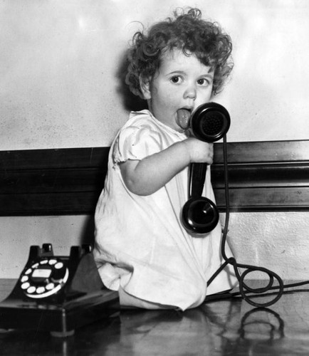 Little girl plays with a telephone