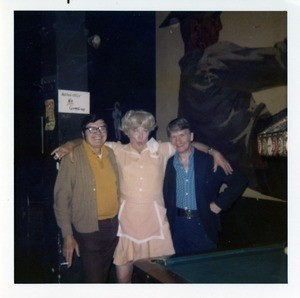 Fallen Angel threesome in front of cowboy art and waitress drag