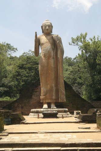 Standing Buddha statue at center of image house
