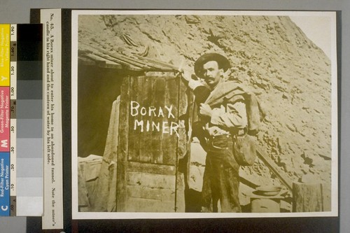 A Borax miner about to enter his home in an abandoned tunnel. Note the miner's candle in his right hand and the canteen of water by his left side