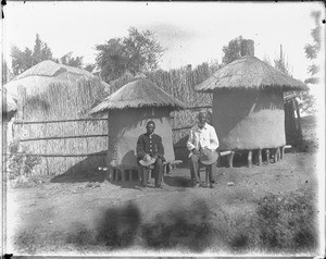 African men sitting in front of granaries, Shilouvane, South Africa