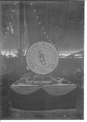 Gravenstein Apple Show display of the Sebastopol Berry Growers, Inc. with a large round sign made of apples and berries on a table with boxes of apples, about 1912