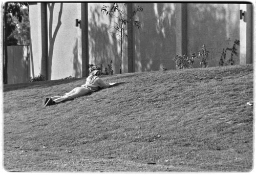 Student laying on grass, near the Recreational Gym