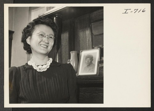Mrs. Peter Sugawara is shown with a picture of her husband, Cpl. Peter Sugawara. Cpl. Sugawara is serving with the