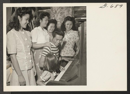 Gathered around the piano for some singing are several members of the Yamasaki family with a couple of their friends
