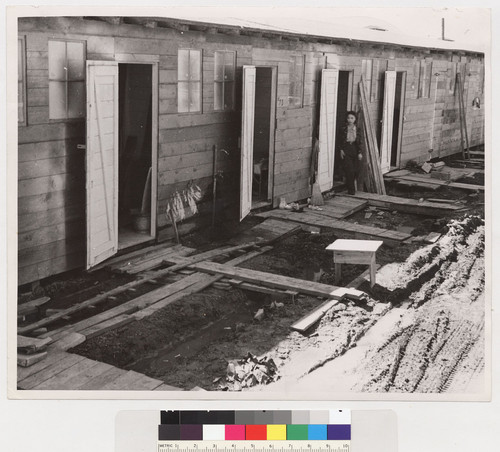 C-324. 4/29/42. Tanforan Assembly Center, San Bruno, California. Barracks for family living quarters. Each door enters into a family unit of two small rooms (remodeled horse-stalls.) Tanforan Assembly Center was opened two days before the photograph was made. On the first day there had been a heavy rain. When a family has arrived here the first step of evacuation is completed