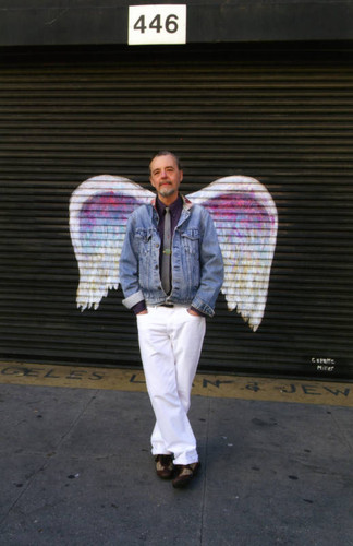 Unidentified man in white pants posing in front of a mural depicting angel wings