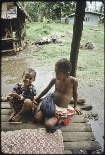 Children sitting on house veranda next to woven mat, girl (r) wears short fiber skirt and turtle-shell earrings
