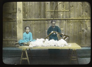 Two people working cotton on a table, China, ca.1917-1923