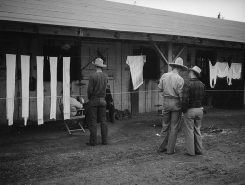 Men in front of stables at the Los Angeles County Fair