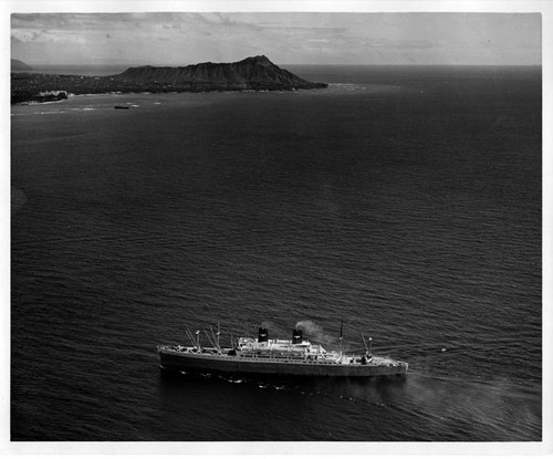 """S.S. Pres. Cleveland in Honolulu. 1948."" Aerial shot; Diamond Head in background"