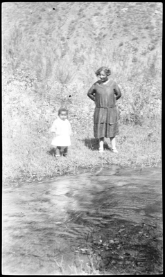 Gloria Pearl Roberts [?] and Pearl Roberts standing next to river bank