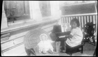 Gloria Pearl Roberts [?] playing toy piano on front porch