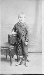 Unidentified young boy, about 6 years old standing next to a Victorian chair in a studio photo, about 1860s